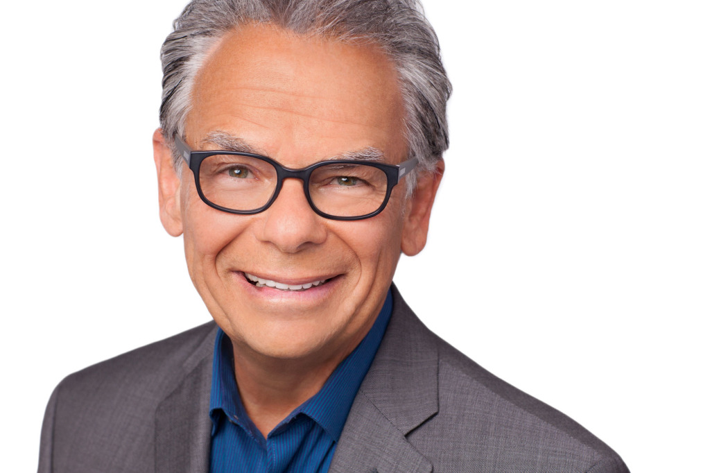 Headshot of smiling man with glasses on white background.