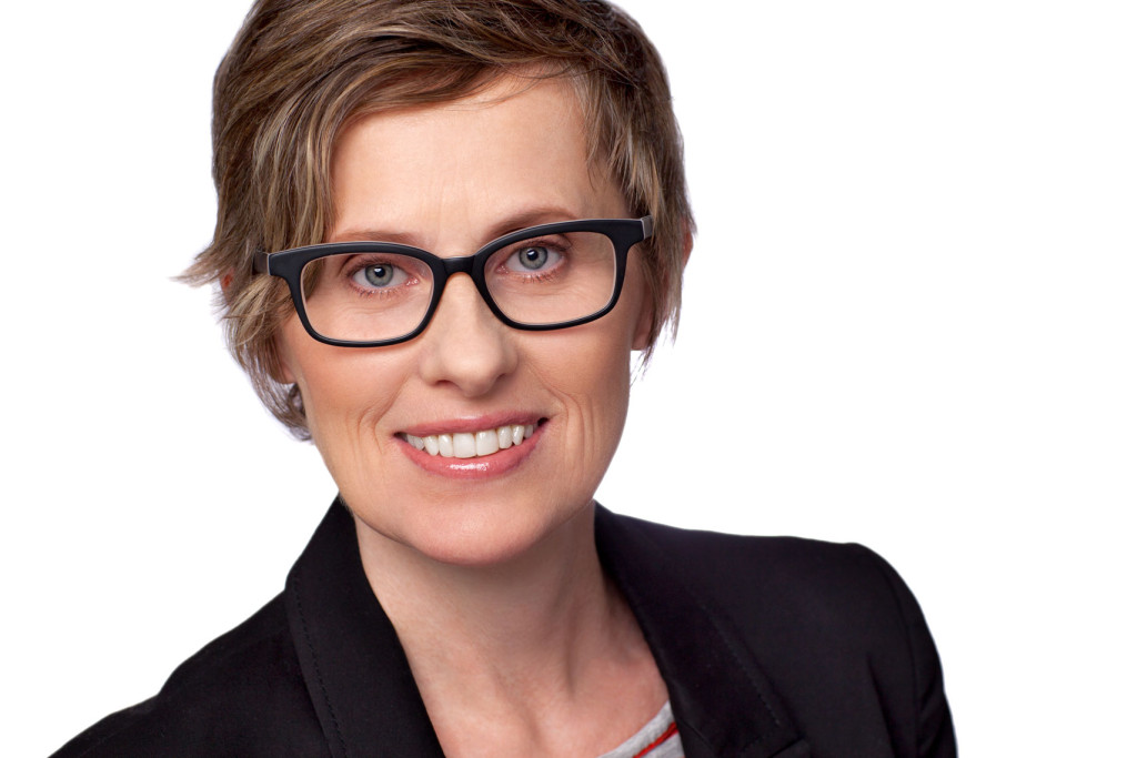 Headshot of woman with black glasses, short blonde hair, blue eyes. Photographed on white background.