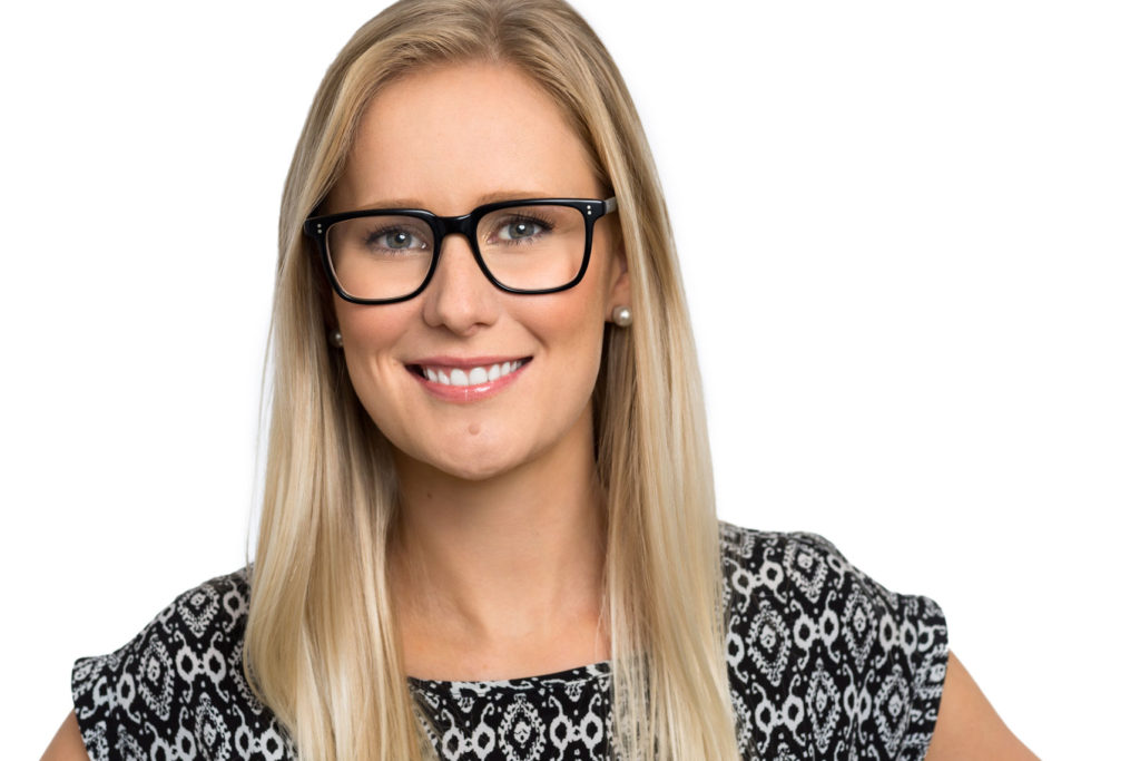 HEadshot of smiling blonde woman with black glasses