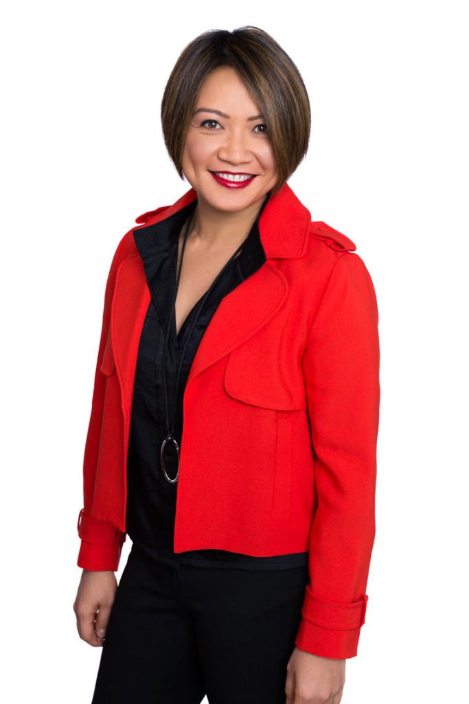 Woman in red jacket in 3/4 body company headshot.