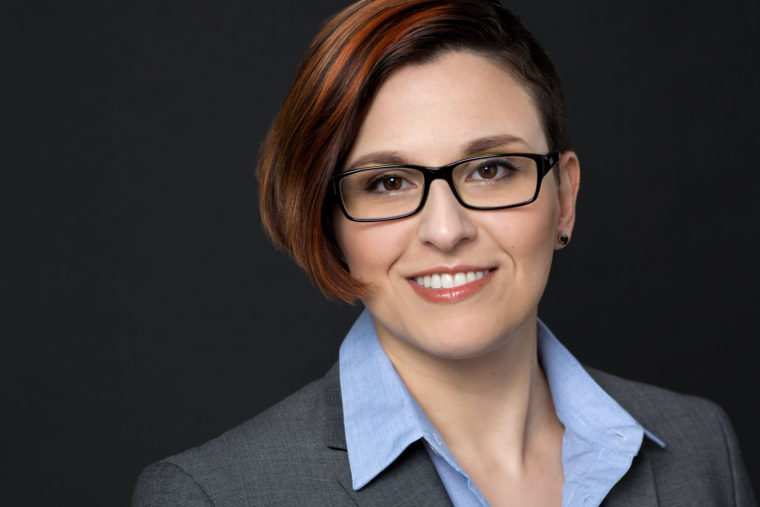 Headshot of smiling woman in suit and glasses