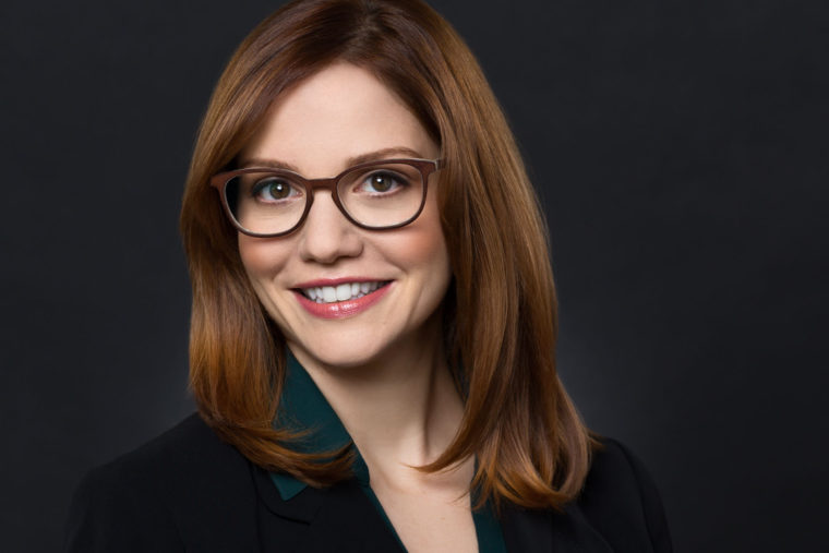 Headshot of Woman CEO with Red Hair and Glasses