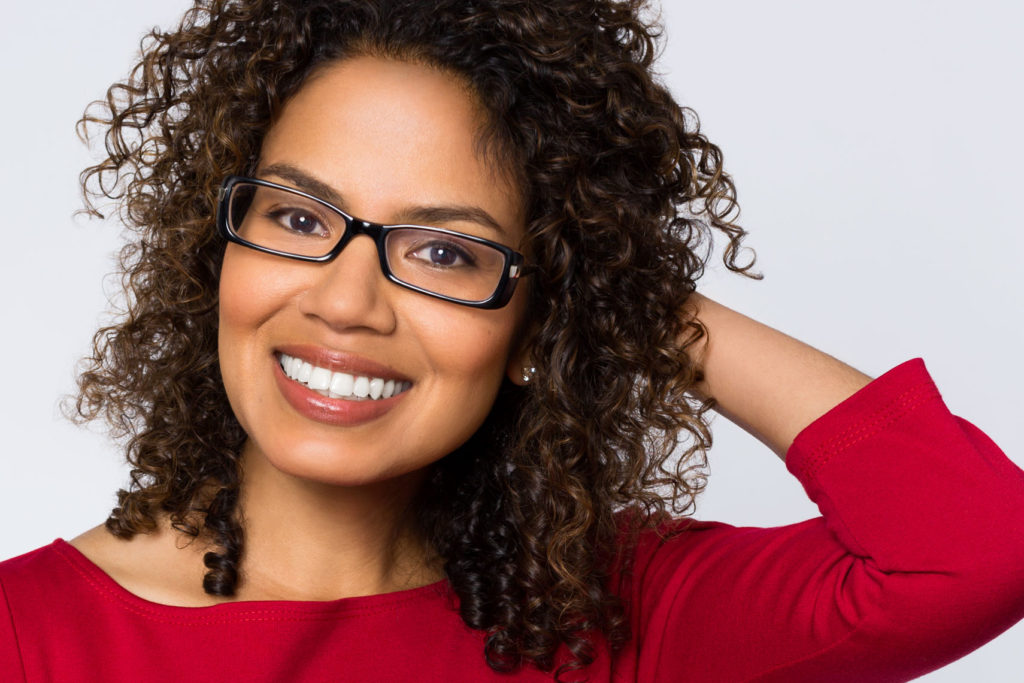 Headshot of smiling woman with curly hair and glasses