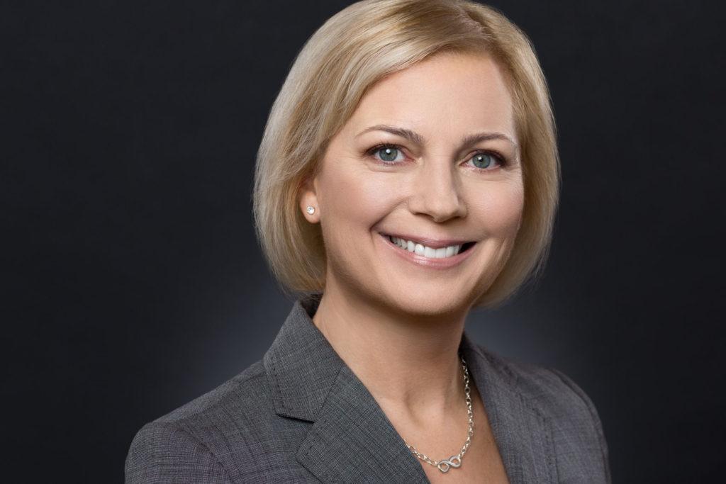Heidi Scheutzes grey blazer and blonde hair contrast well with the black background in this headshot.