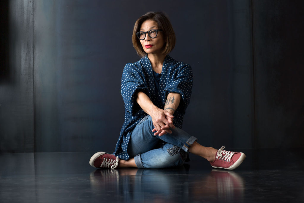 Portrait of Woman with glasses and arm tattoo sitting cross legged in front of a metal background.
