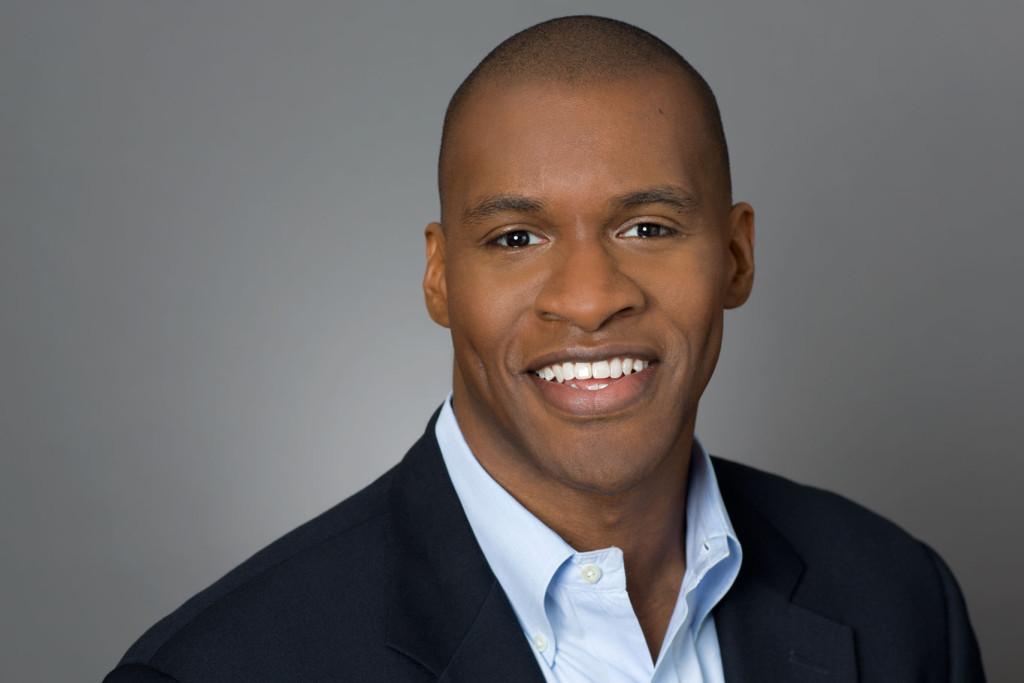 Company Headshot of man in blazer on a grey background.
