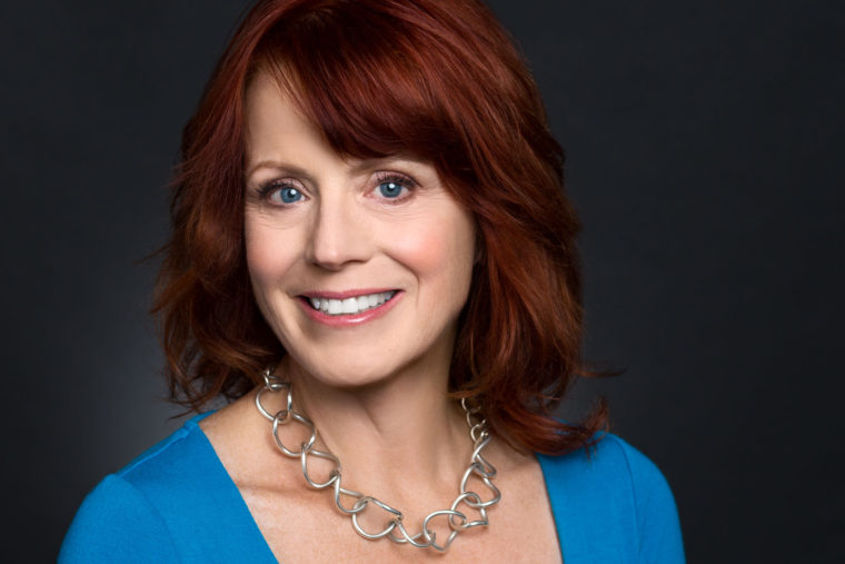 headshot of smiling woman with red hair and blue eyes
