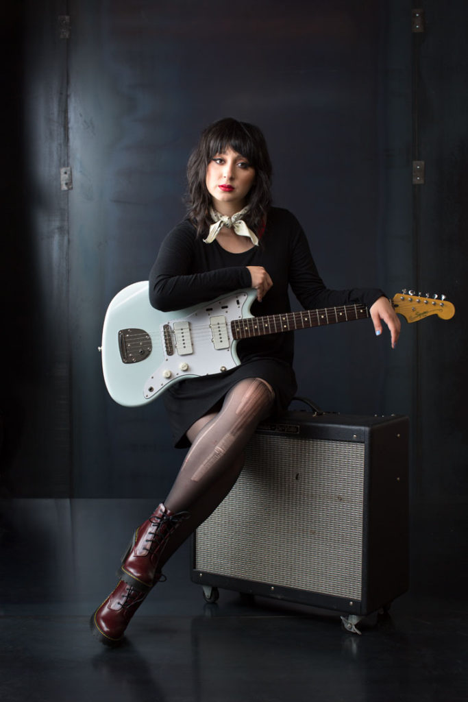 Woman Musician sits on an amp with her guitar