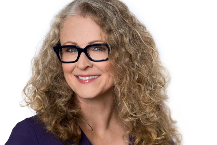 Headshot of smiling woman with black glasses and curly blonde hair