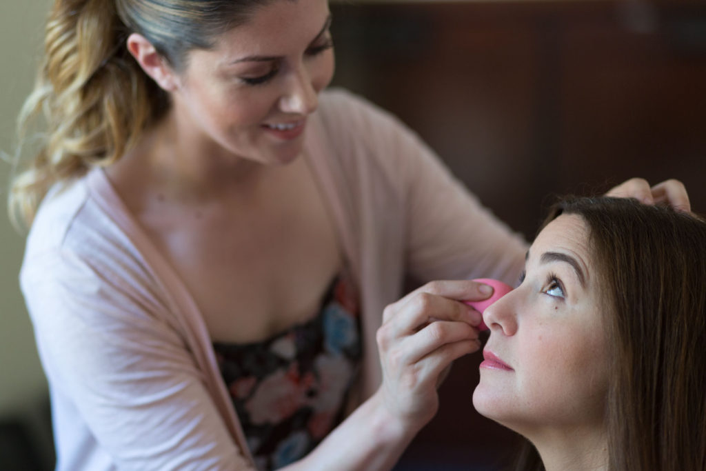 Makeup artist applies makeup before a corporate photo session