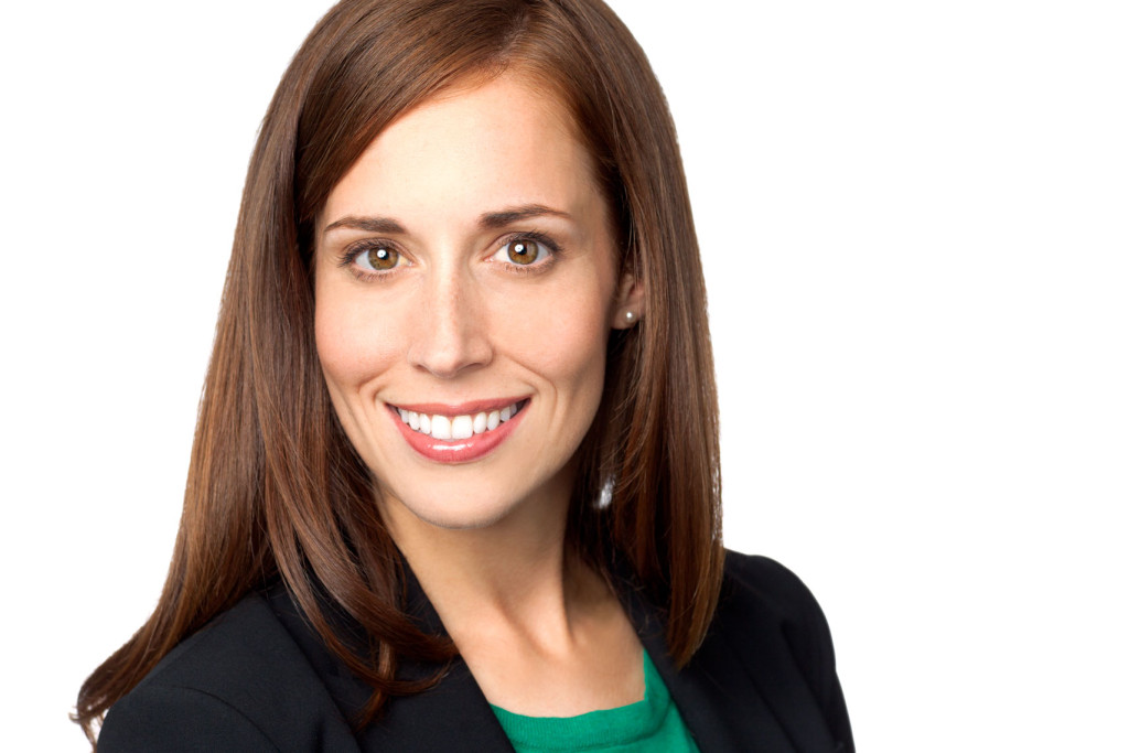 Headshot of smiling woman in black suit and green blouse on white background.