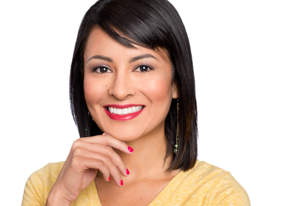 Woman in yellow sweater uses her hand in this headshot on a white background.