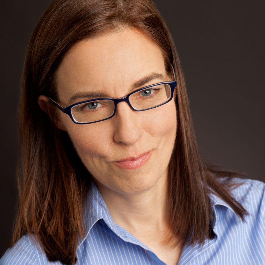 Headshot of Molly Hartle with straight brown hair, blue glasses and a blue shirt on a black background.