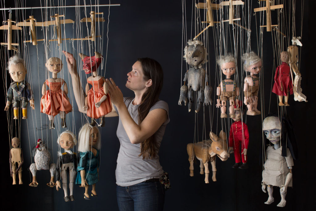 Puppeteer and Marionettes in fron of a metal Background