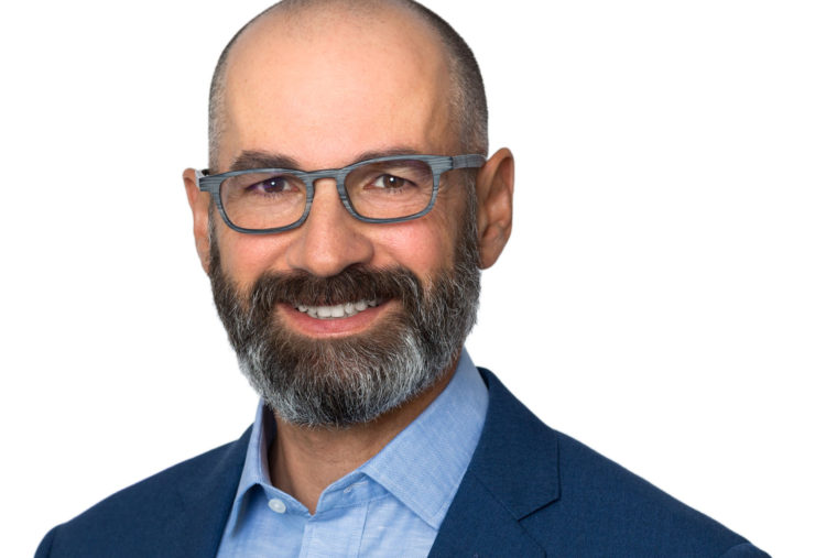 Headshot of smiling man with beard and glasses