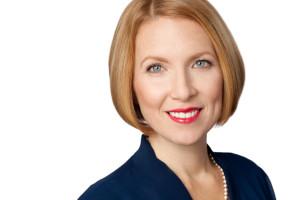 Headshot of blonde woman with blue eyes on white background.