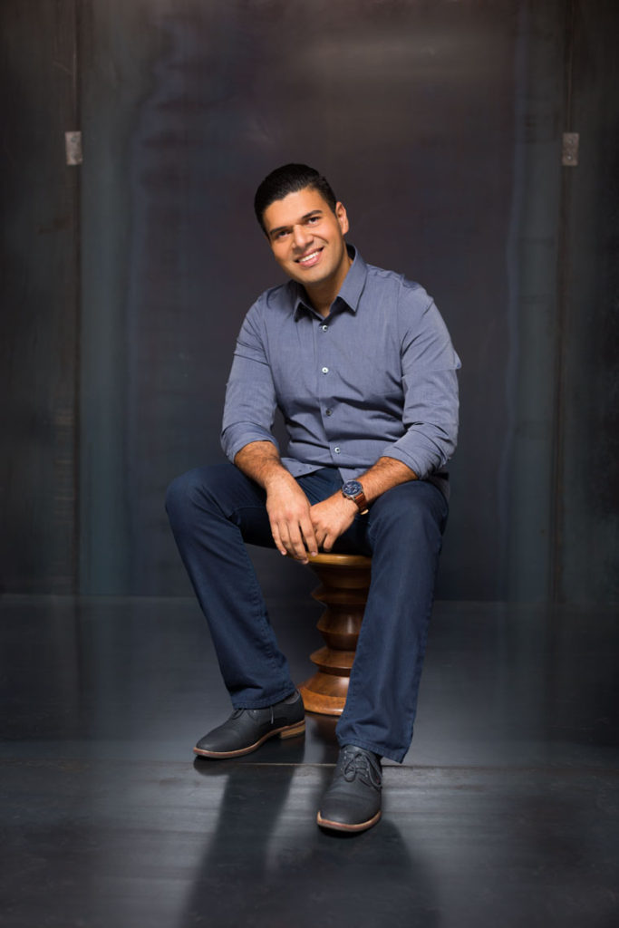 Portrait of Actor sitting on an Eames Stool  in front of a Metal Background