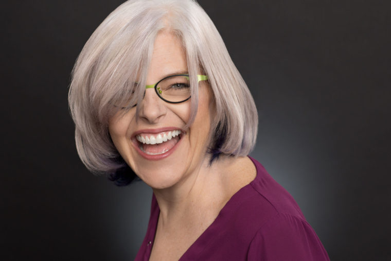 Headshot of laughing woman with white hair and green glasses