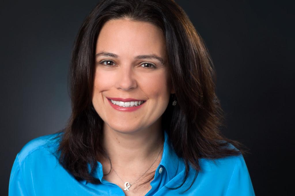 Headshot of Author Tracy Sestili in blue shirt on black background.